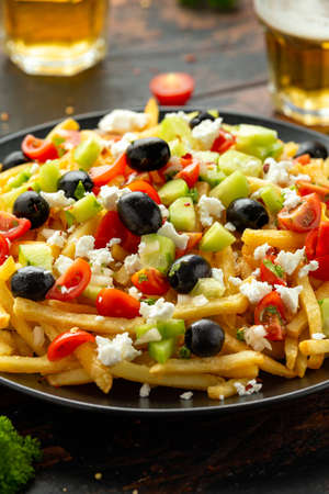 Loaded potato Vegan Fries with tomato, cucumber, olives and feta cheese.