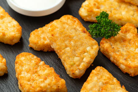 Hash brown potato patties on rustic stone board.