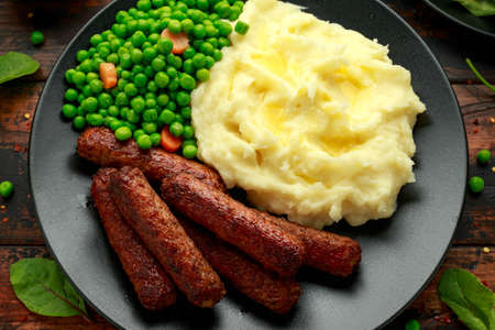 Vegetarian vegan sausages with mashed potato and green peas in black plate