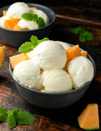 Melon ice cream with mint in bowl on wooden table