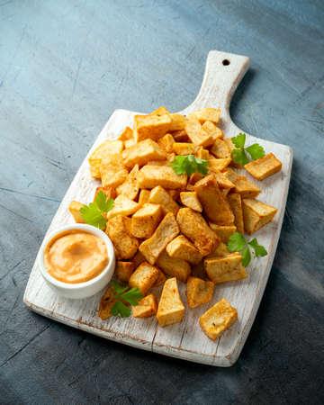 Patatas bravas traditional Spanish potatoes snack tapas on white wooden board 스톡 콘텐츠