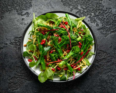 Tenderstem broccoli and egg noodles Asian style vegetarian salad with roasted pine nuts and pomegranate seeds