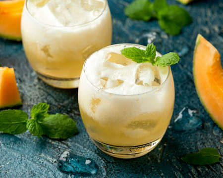 Refreshing Cantaloupe Melon cocktail with ice and mint on rustic table
