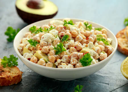 Chickpeas salad with feta cheese, avocado and herbs in white bowl. healthy food 스톡 콘텐츠