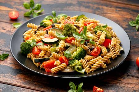 Fusilli pasta with vegetable, broccoli, zucchini, red pepper, eggplant, tomato and basil on black plate