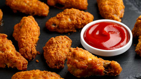 Spicy deep fried Chicken wings with ketchup on stone board