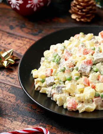 Christmas and New year Olivier salad, traditional Russian food with decoration, gifts, green tree branch on wooden rustic table 스톡 콘텐츠