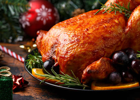 Christmas Chicken, roast in oven with decoration, gifts, green tree branch on wooden rustic table