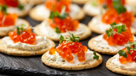 Salmon caviar and soft cheese savory crackers with sesame and poppy seeds served on black slate board