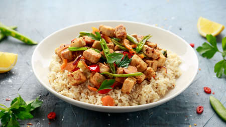Vegetarian meat free mycoprotein pieces vegetable stir fry, brown rice served in white plate Archivio Fotografico
