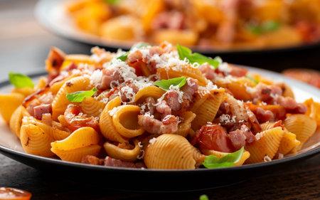 Conchiglie alla Amatriciana pasta with pancetta bacon, tomatoes and pecorino cheese. Healthy Italian food Stock Photo