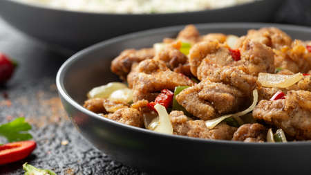 Stir fry chinese salt and pepper chicken with rice in grey bowl