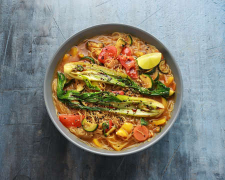 Asian style Pak choi, lemongrass, and ginger curried noodles served with lime wedges Stockfoto
