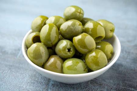 Italian green olives in white bowl.