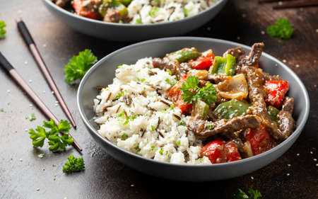 Stir fry Chinese pepper beef steak with onion, red and green bell pepper, rice in bowl