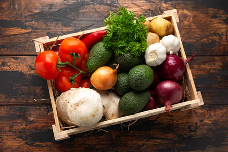 Fresh Vegetables in wooden box on rustic table Stockfoto
