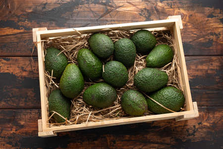 Fresh avocado in wooden box on rustic table