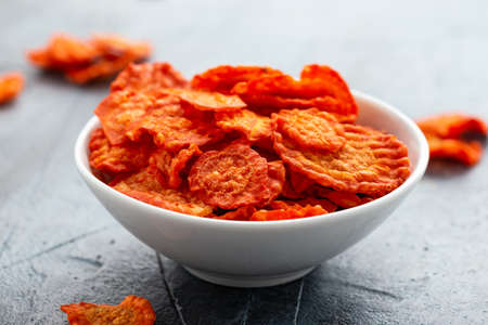 Healthy baked carrot chips in white bowl Stockfoto