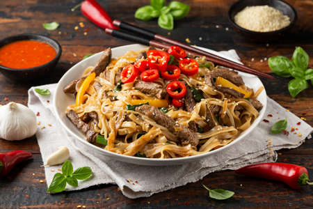 Stir fry Beef Chow Fun with rice noodles, bean sprouts, spring onions and chili.