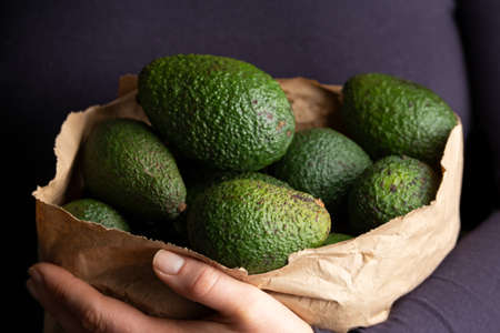 Woman holding paper carrier bags, full of fresh avocado. Healthy food.