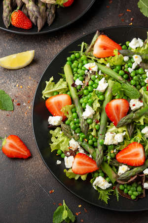 Asparagus and Strawberry Salad with vegetables, green peas and feta cheese in black plate. healthy food.