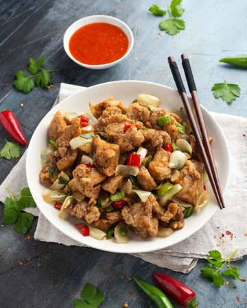 Stir fry chinese salt and pepper chicken with red, green chilli, onion, spring onion in white bowl.
