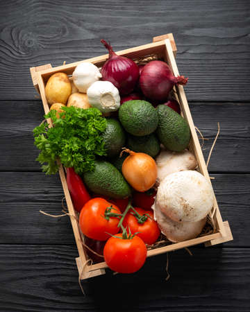 Fresh Vegetables in wooden box on dark wooden background Stockfoto