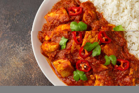 Spicy Chicken Pathia curry with basmati rice in a white plate. healthy food.