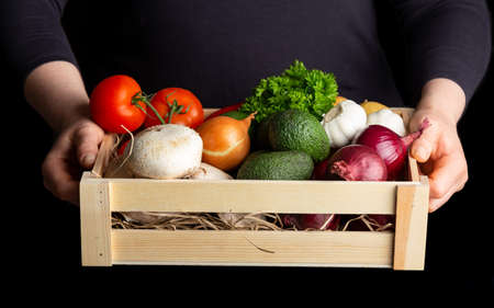 Woman holding wooden box full of fresh raw vegetables. Healthy food. Stockfoto