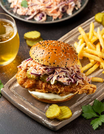 Fried chicken burger, sandwich with coleslaw, pickled gherkins, mayonnaise and beer. Fast food.