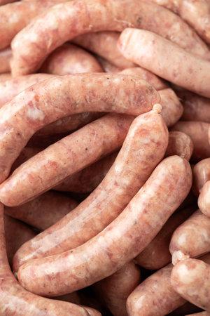Raw pork chipolata sausage in cast iron skillet frying pan