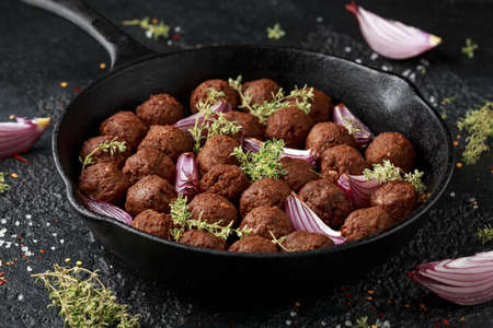 Thyme and onion vegetarian vegan meatballs oven baked in cast iron skillet frying pan Stockfoto