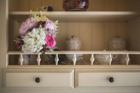 Bride bouquet in a kitchen shelf photo