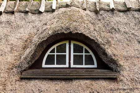 old window in a thatched roof