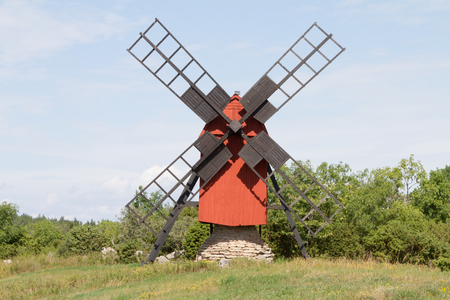 A small windmill stands on a stone pile