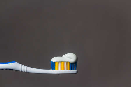 toothbrush with toothpaste isolated on grey background. Archivio Fotografico