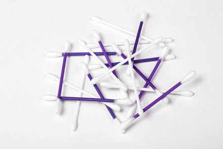 white and purple cotton buds on white background, hygiene concept
