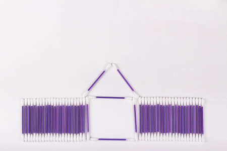 house of purple cotton buds on a white background, hygiene concept, copy space