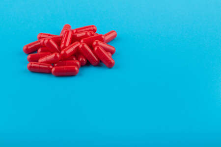Heap of red pills (capsules) on a blue background, close-up Kho ảnh
