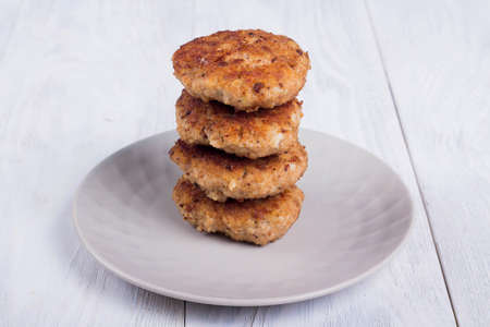 cutlets on a gray plate, on a white wooden background, Burger ingredients
