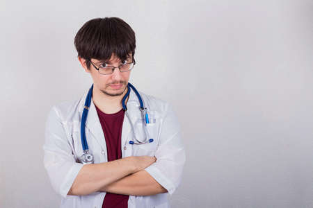 male doctor standing with stethoscope, medicine concept, gray background