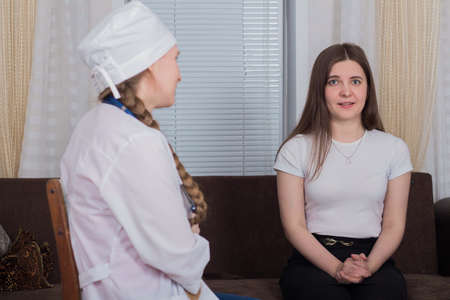Female patient receives medical consultation from female doctor at home, medicine concept Archivio Fotografico