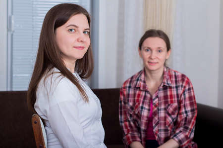 Female patient receives medical advice from female doctor at home, medicine concept