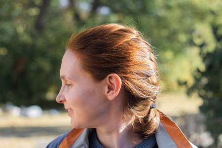 Portrait profile of a red-haired woman in the sunlight