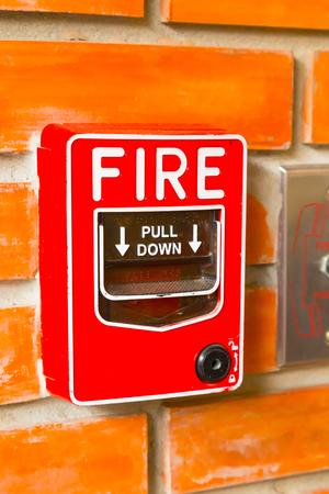 Fire Alarm Switch on the orange brick wall background texture. Foto de archivo