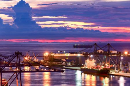Achtergrond voor kranen en industriële vrachtschepen in de haven bij schemering.