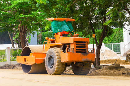 steamroller: An operator backs a steamroller over dirt to prepare for a construction siteOperating a SteamrollerAn operator backs a steamroller over dirt to prepare for a construction site.