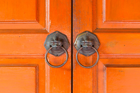 Lions handles hang on a traditional Chinese door.