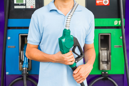 Man hold fuel nozzle to add fuel in car at gas station. Zdjęcie Seryjne - 70258662