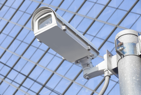 CCTV installed on the pole in front of the building windows. Stock Photo